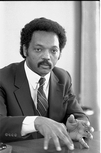 Jesse Jackson, half-length, seated at table, wearing jacket and tie, gesturing with his hands