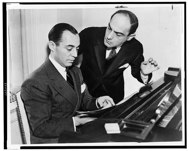 Richard Rodgers seated at piano with Lorenz Hart on right