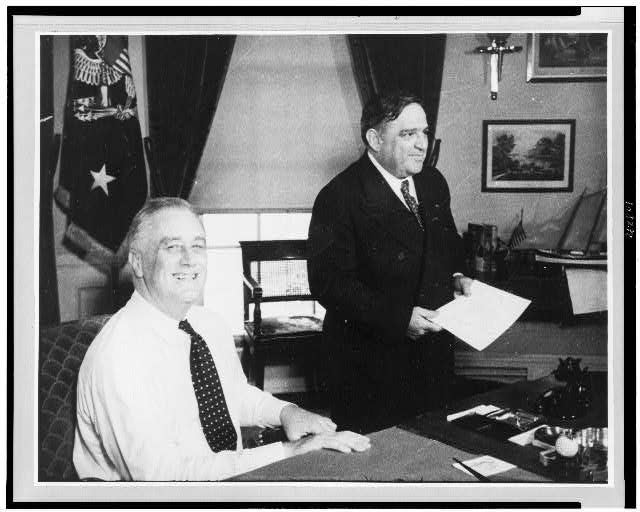 Franklin D. Roosevelt, half-length portrait, seated at desk, facing right, with Fiorello La Guardia