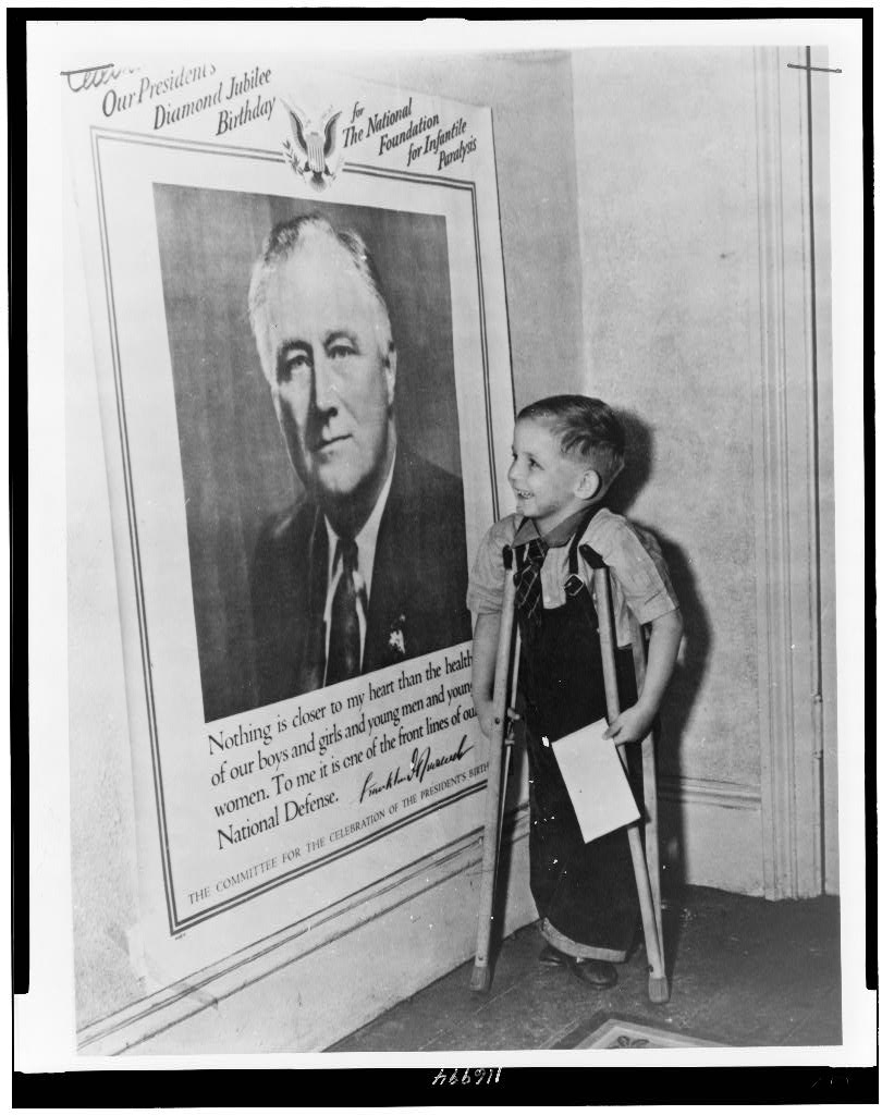 Gerry King, four years old, who suffers from infantile paralysis, looking at poster of Franklin D. Roosevelt